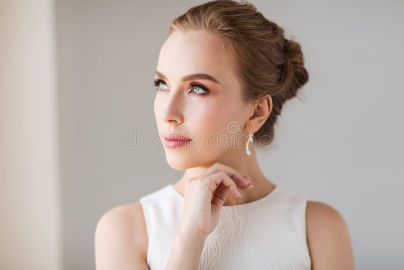 Mulher de sorriso no vestido branco com joia do diamante fotos de stock
