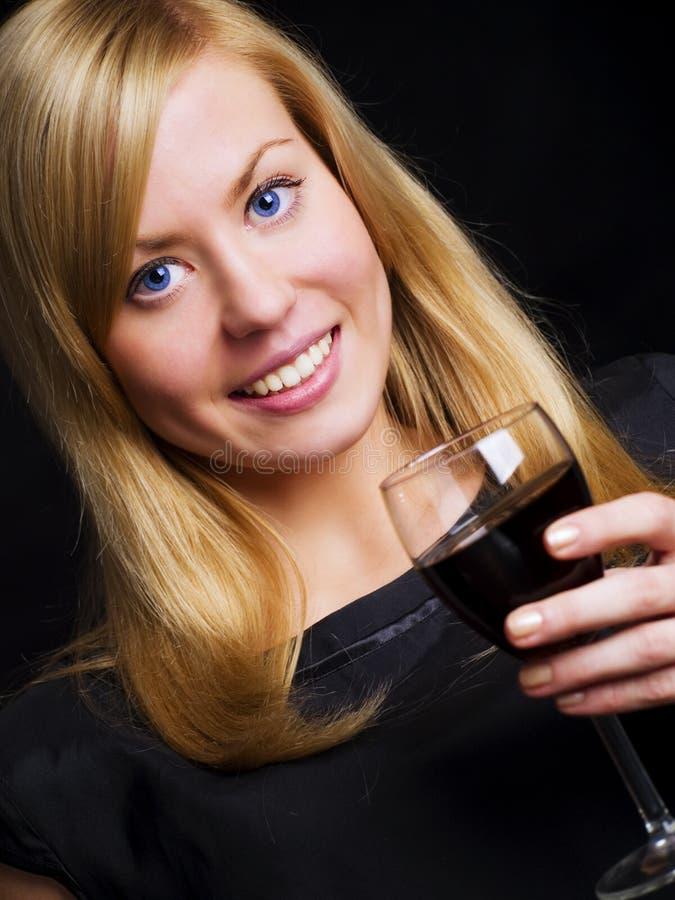 Mulher de sorriso no vinho preto da terra arrendada do vestido fotografia de stock