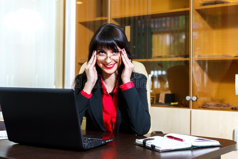 A mulher de sorriso nos vidros trabalha no escritório imagem de stock