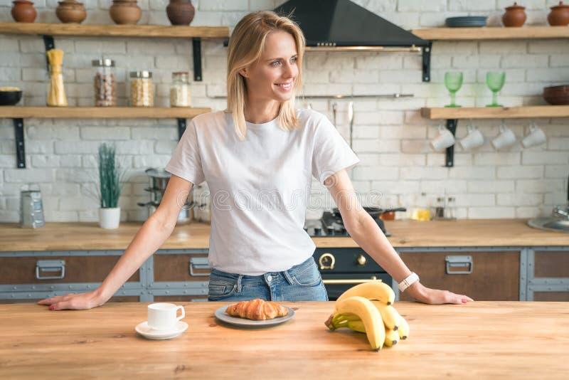 A mulher de sorriso nova bonita está preparando o café da manhã na cozinha em casa, olhando afastado café da manhã, croissant, ba foto de stock