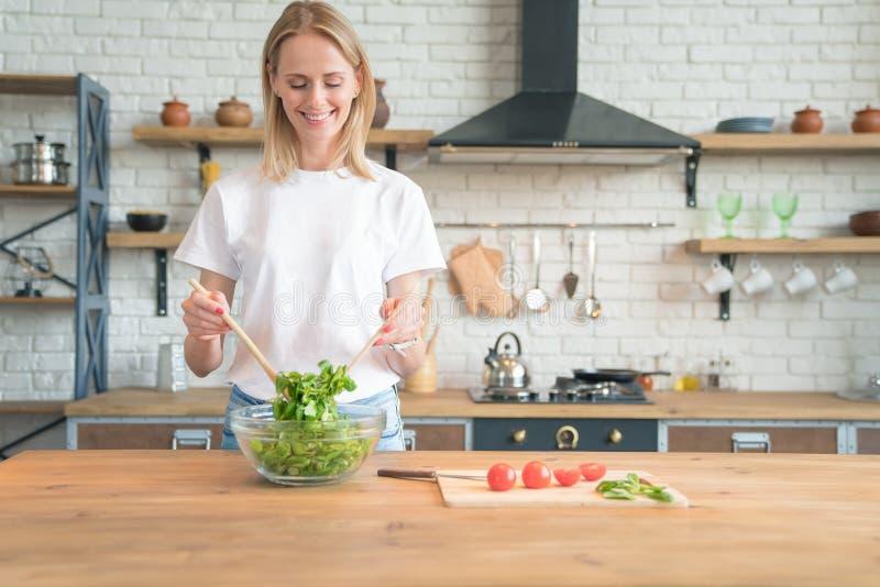 Mulher de sorriso nova bonita que faz a salada na cozinha Alimento saud?vel Salada vegetal Dieta Estilo de vida saud?vel Coziment imagem de stock