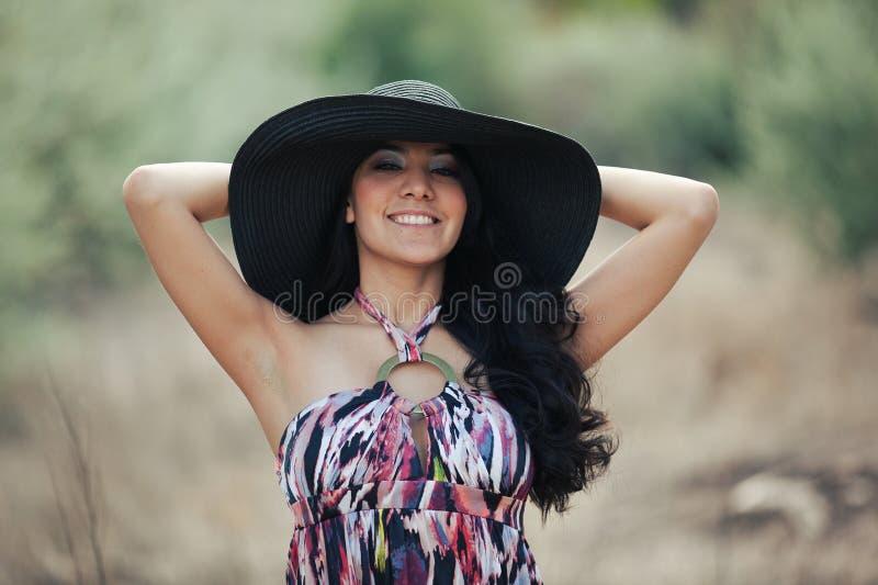 Mulher de sorriso nova com chapéu fotos de stock