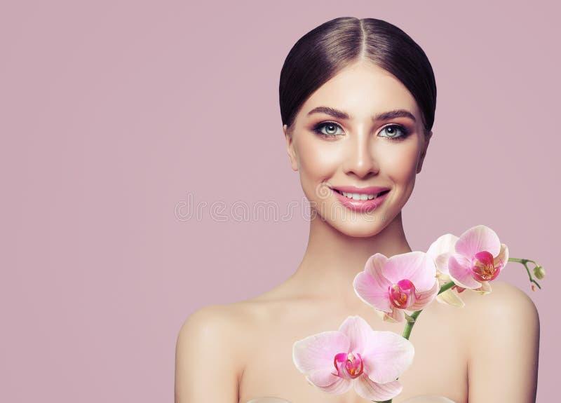 Mulher de sorriso nova com composição e flores da orquídea fotos de stock royalty free