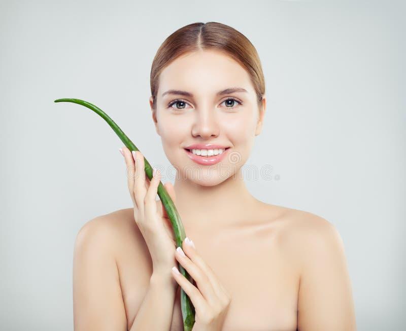 Mulher de sorriso nova com a folha de vera do aloés fotografia de stock