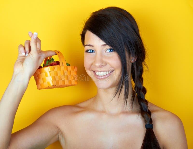 Mulher de sorriso nova com morangos imagem de stock royalty free