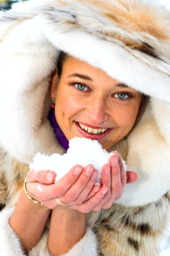 Mulher de sorriso nova com neve nas mãos fotos de stock royalty free