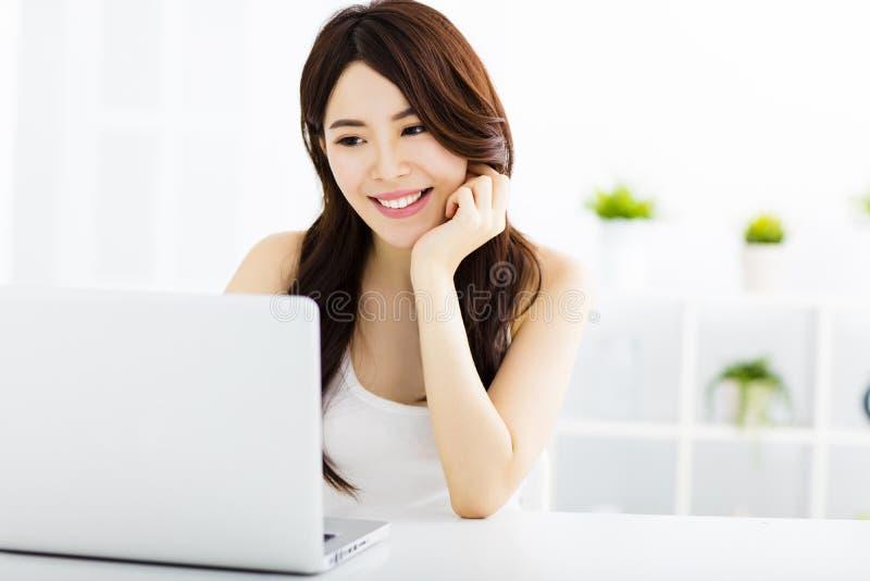 Mulher de sorriso nova com portátil fotografia de stock