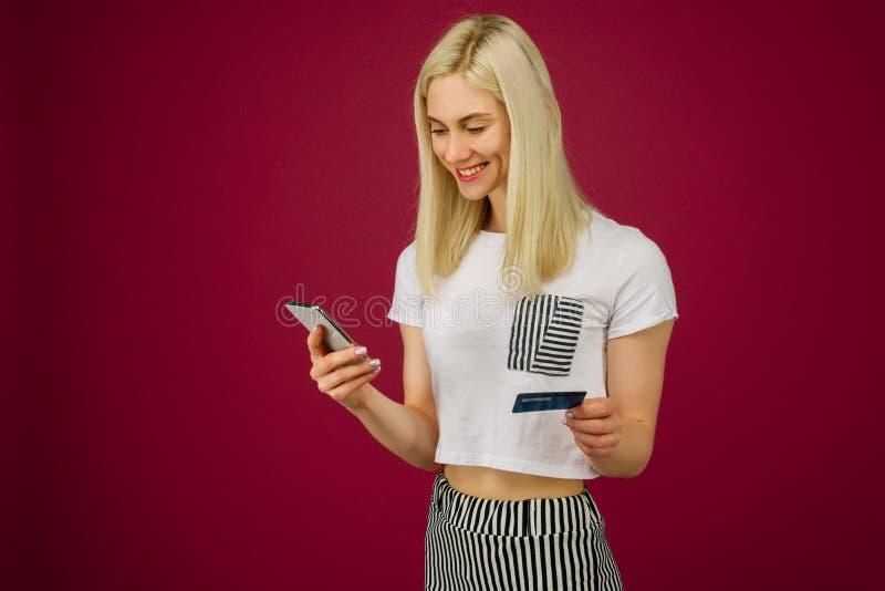 A mulher de sorriso nova compra em linha Guarda um smartphone e um cartão de crédito à disposição fotos de stock