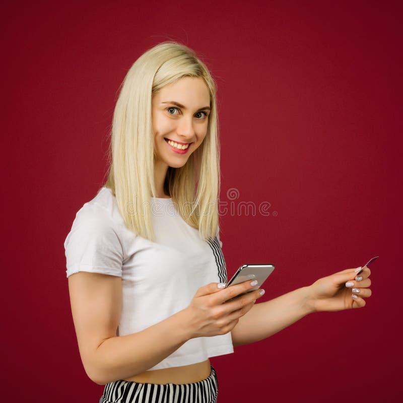 A mulher de sorriso nova compra em linha Guarda um smartphone e um cartão de crédito à disposição imagens de stock