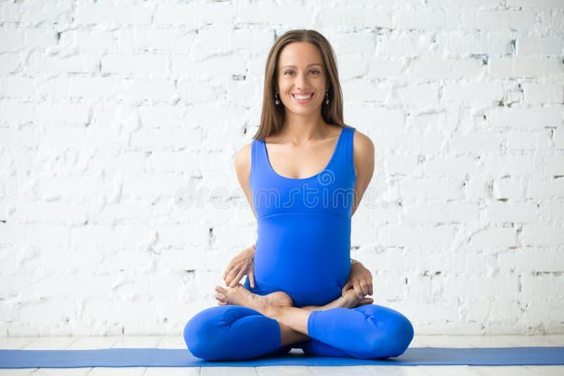 Mulher de sorriso nova em pose encadernada de Lotus, fundo branco do estúdio imagem de stock