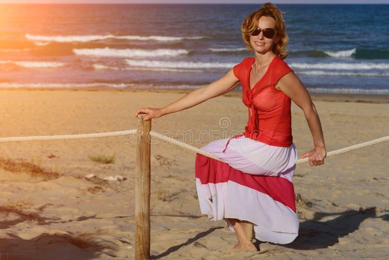 Mulher de sorriso nova em um vestido espanhol com os óculos de sol que sentam-se na cerca de madeira da corda na praia mediterrân fotografia de stock royalty free