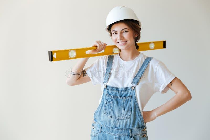Mulher de sorriso nova no capacete de segurança que guarda a ferramenta nivelada amarela foto de stock