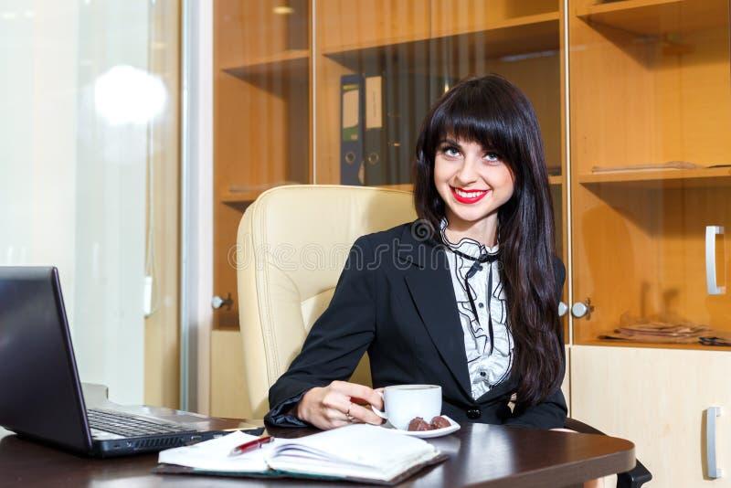 Mulher de sorriso nova no escritório que guarda uma xícara de café fotografia de stock
