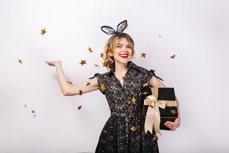 A mulher de sorriso nova no fundo branco com a caixa de presente, comemorando o evento brightful, festa de anos, veste elegante fotografia de stock
