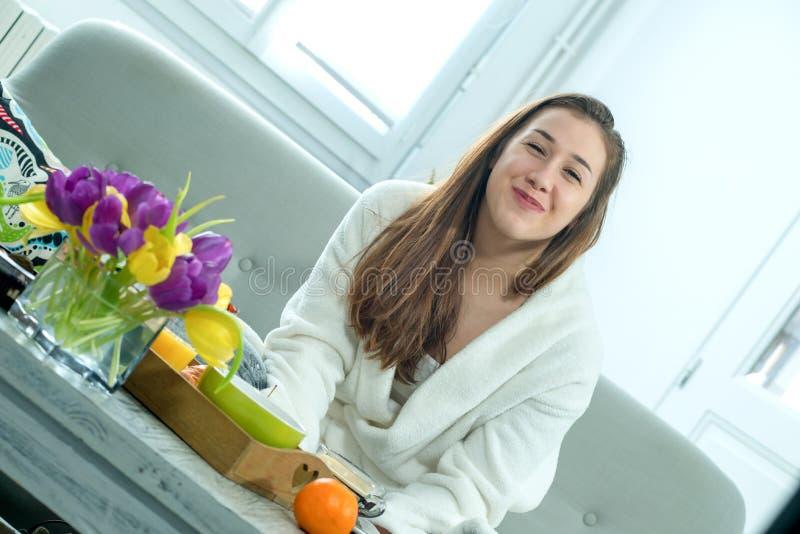 Mulher de sorriso nova no roupão que senta-se no sofá imagens de stock royalty free