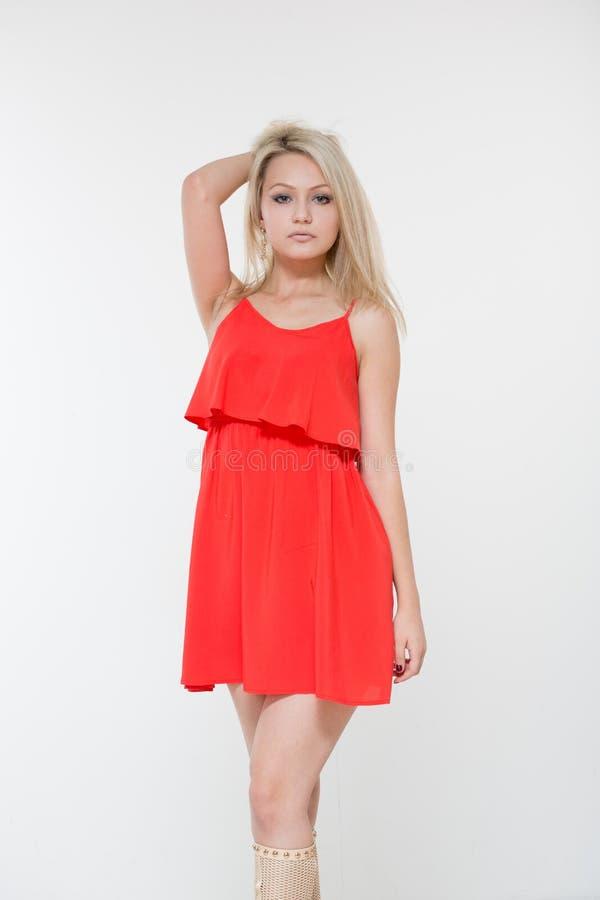 Mulher de sorriso nova no vestido vermelho Isolado sobre o fundo branco fotos de stock royalty free