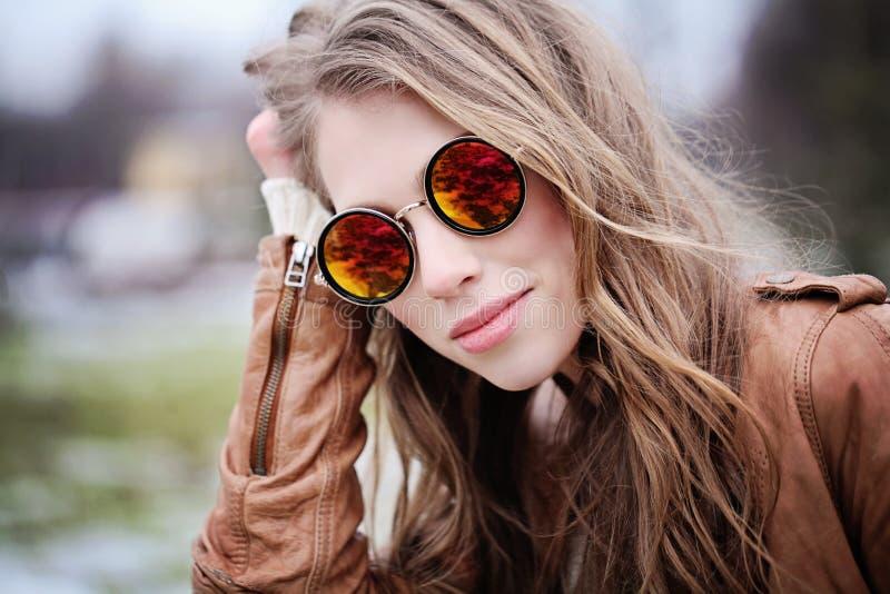 Mulher de sorriso nova nos óculos de sol que olham a câmera foto de stock