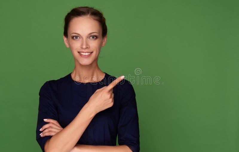 Mulher de sorriso nova que aponta o dedo fotografia de stock