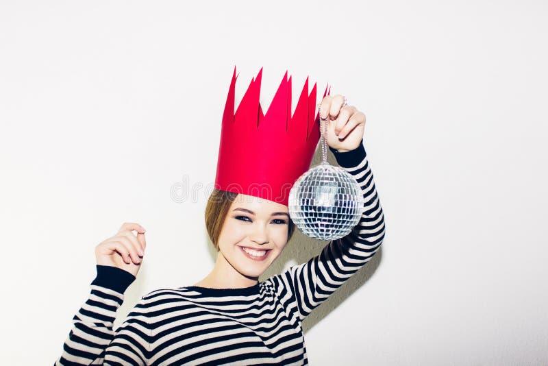 Mulher de sorriso nova que comemora o partido, o vestido descascado vestindo e a coroa de papel vermelha, bola dinâmica feliz do  imagens de stock royalty free