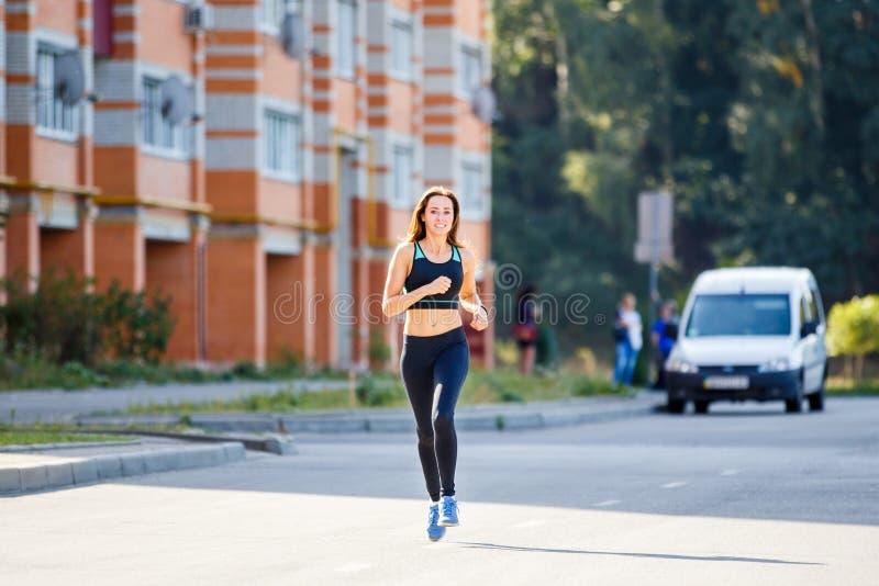 Mulher de sorriso nova que corre na estrada na manhã fotografia de stock royalty free
