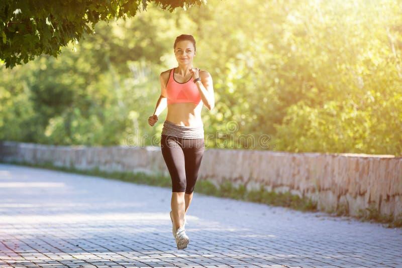 Mulher de sorriso nova que corre no parque na manhã imagens de stock royalty free