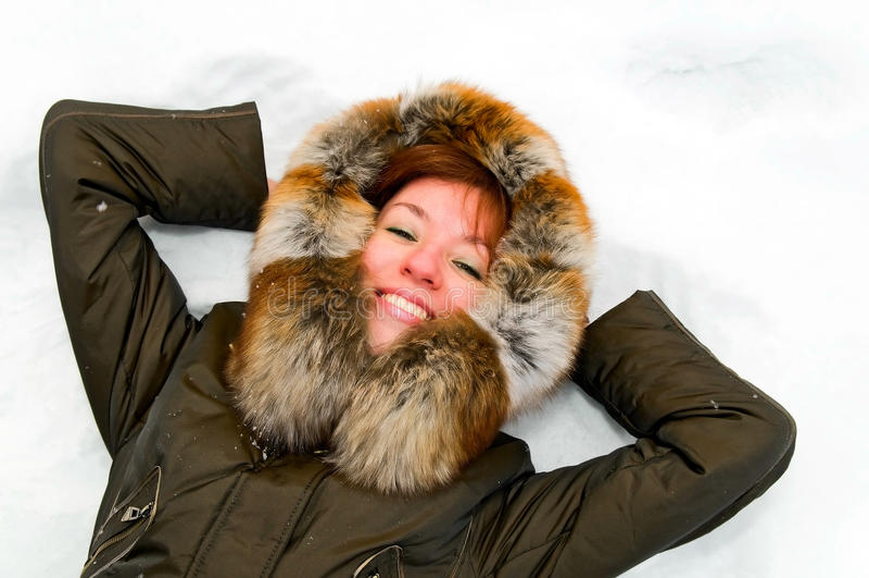 Mulher de sorriso nova que descansa na neve fotos de stock