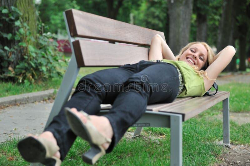 Mulher de sorriso nova que encontra-se no banco ao ar livre fotografia de stock royalty free