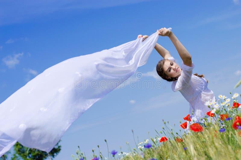 Mulher de sorriso nova que está no campo de trigo amarelo que guardara uma parte de pano longa branca no vento. foto de stock royalty free