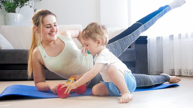 Mulher de sorriso nova que faz o exercício da aptidão quando sua criança que joga com os brinquedos ao lado dela foto de stock royalty free