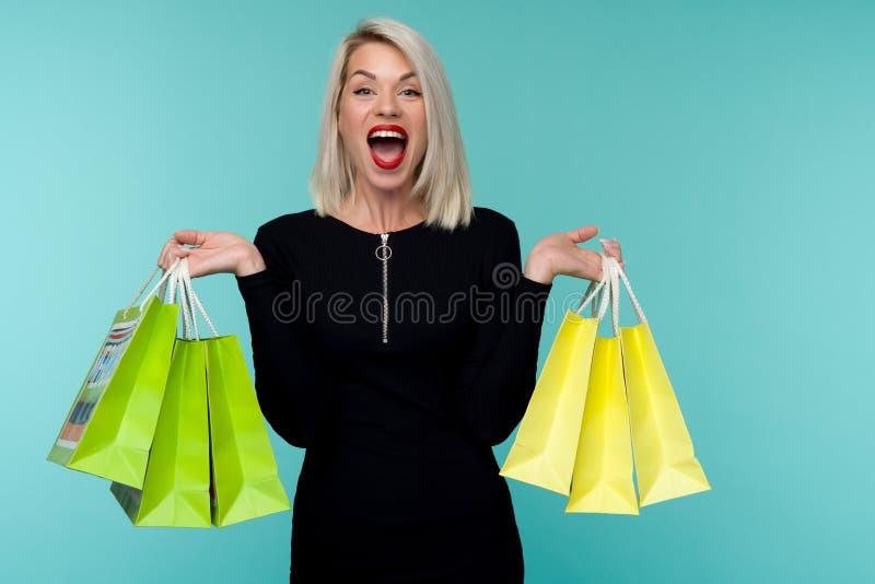 Mulher de sorriso nova que guarda sacos de compras no feriado preto de sexta-feira menina feliz no fundo azul fotografia de stock