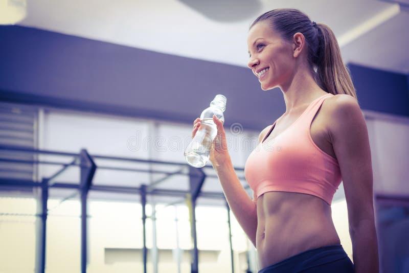 Mulher de sorriso nova que guarda uma garrafa da água foto de stock