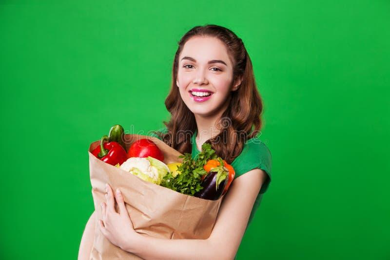 Mulher de sorriso nova que mantém um saco completo de saudável imagem de stock