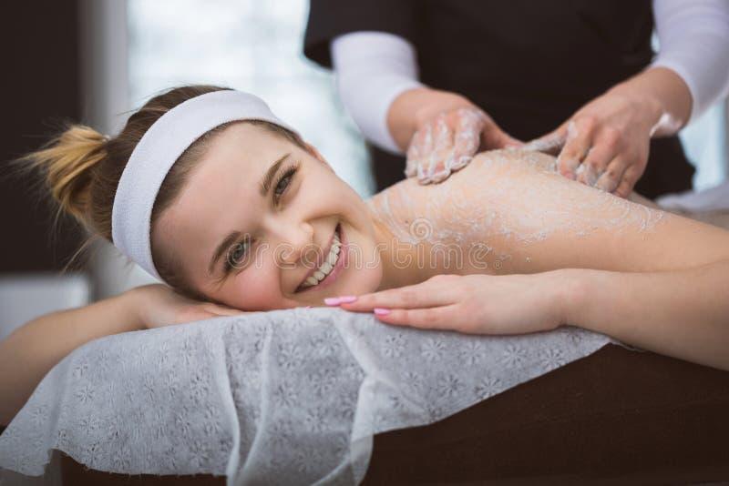 A mulher de sorriso nova que obtém de consolidação o açúcar esfrega a terapia em seu b fotografia de stock royalty free
