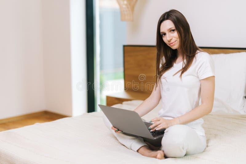 Mulher de sorriso nova que olha a câmera ao sentar-se na cama com portátil imagem de stock royalty free
