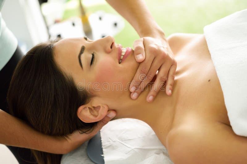 Mulher de sorriso nova que recebe uma massagem principal em um centro dos termas fotografia de stock