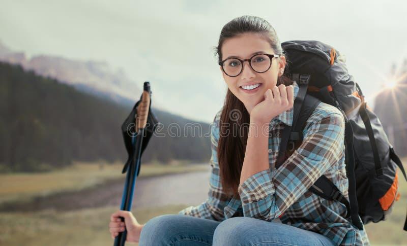 Mulher de sorriso nova que trekking nas montanhas e que tem uma ruptura de relaxamento, é de assento e guardando a caminhada de p fotos de stock