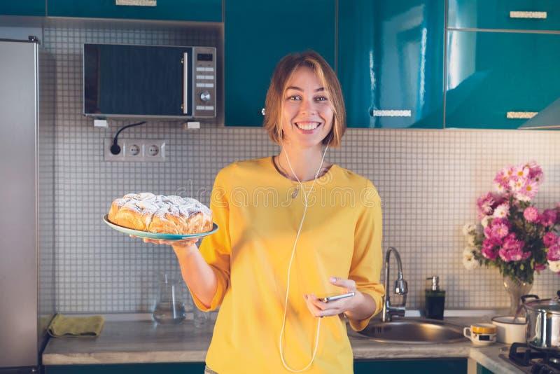 Mulher de sorriso para escutar música nos fones de ouvido e na torta caseiro quente da demonstração Cozinha azul no fundo fotos de stock