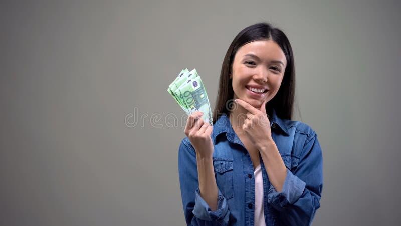 Mulher de sorriso pensativa que guarda os euro, isolados no fundo cinzento, cashback imagens de stock