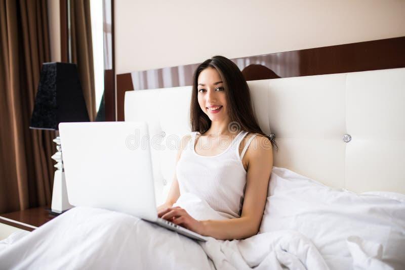 Mulher de sorriso que alcança em seus meios sociais como relaxa na cama com um laptop em uma manhã preguiçosa fotografia de stock