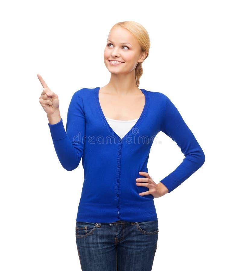 Mulher de sorriso que aponta seu dedo acima foto de stock royalty free