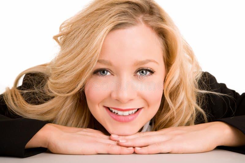 Mulher de sorriso que coloca em sua mesa fotografia de stock royalty free