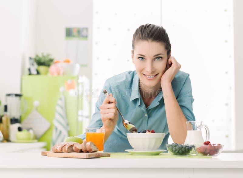 Mulher de sorriso que come o café da manhã em casa imagem de stock royalty free