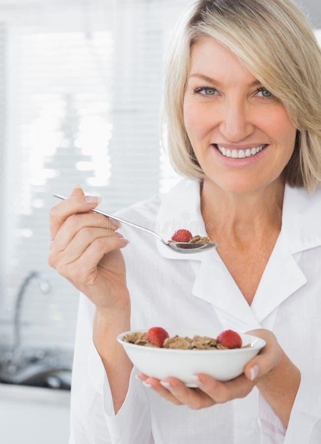 Mulher de sorriso que come o cereal para o café da manhã imagem de stock royalty free