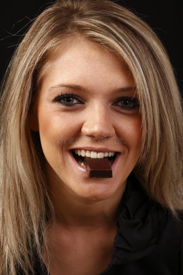 Mulher de sorriso que come o chocolate fotos de stock