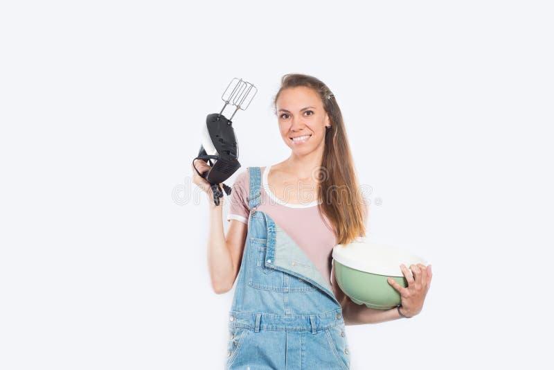 Mulher de sorriso que cozinha no fundo branco vazio fotografia de stock