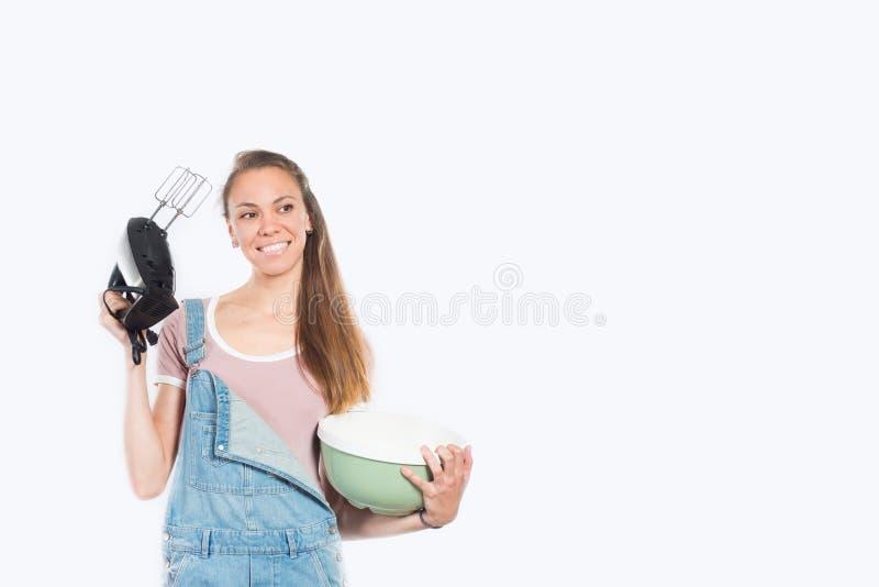 Mulher de sorriso que cozinha no fundo branco vazio imagem de stock royalty free