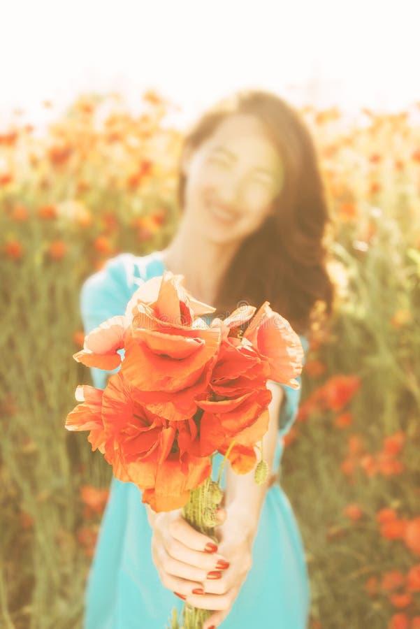 Mulher de sorriso que dá um ramalhete de papoilas vermelhas fotografia de stock royalty free