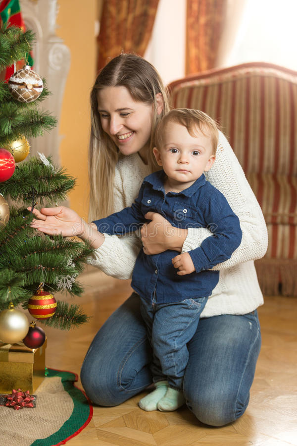 Mulher de sorriso que decora a árvore de Natal com seus 10 meses de b velho fotografia de stock