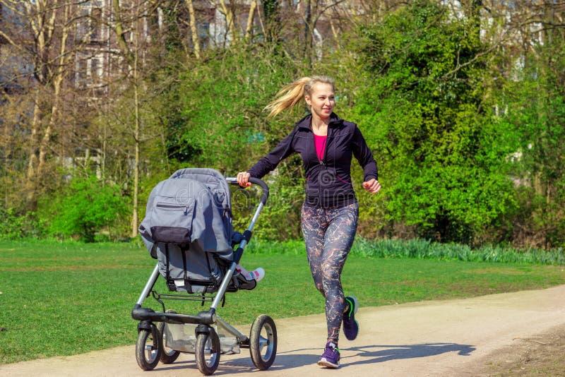 Mulher de sorriso que empurra o carrinho de bebê fotos de stock royalty free