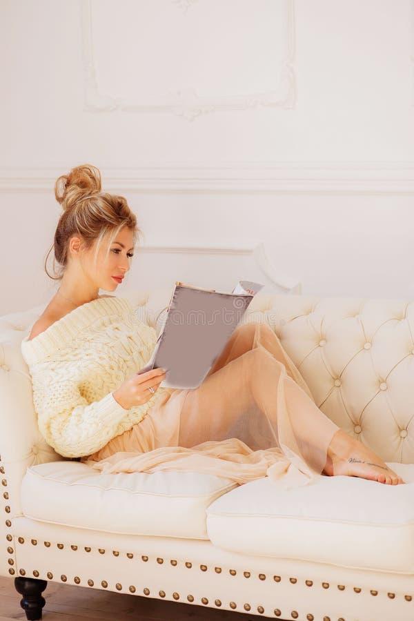 Mulher de sorriso que encontra-se em Sofa Reading um compartimento fotos de stock
